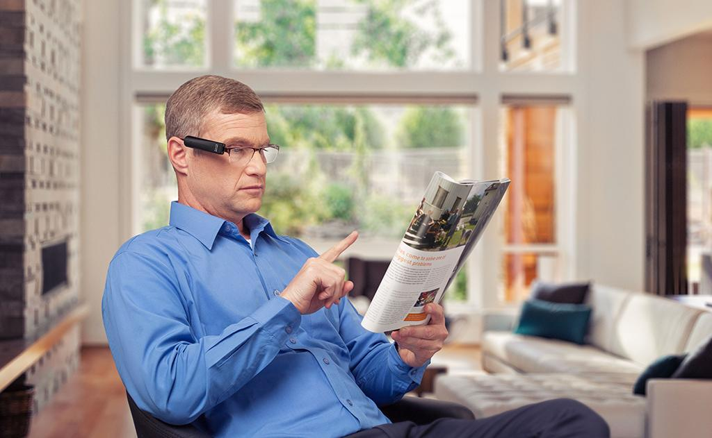 OrCam MyEye 2 being used by a gentleman to read a magazine, he's pictured pointing at the text he's having read aloud