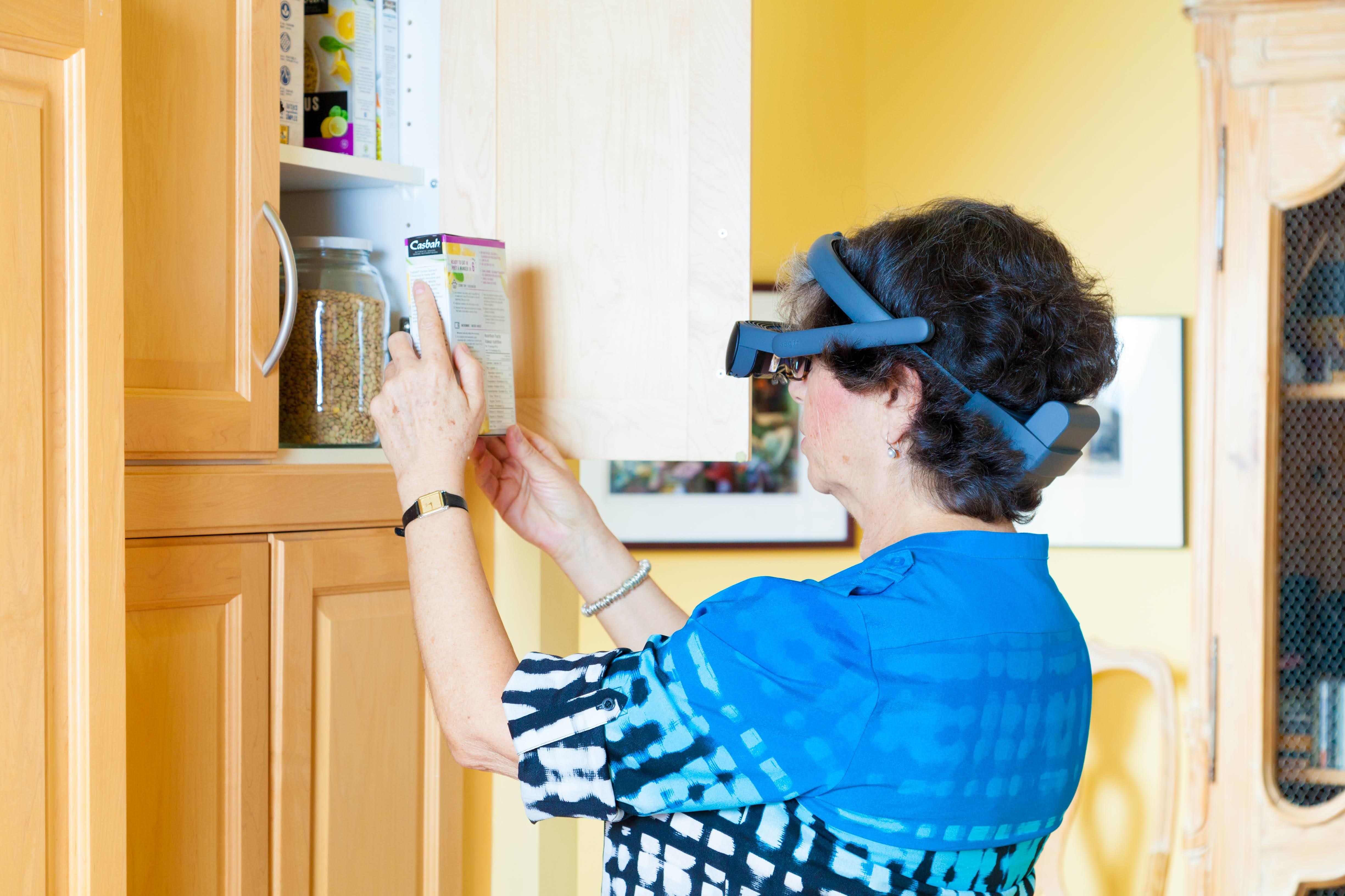 a lady using the esight 4 to read the back of a packet of food