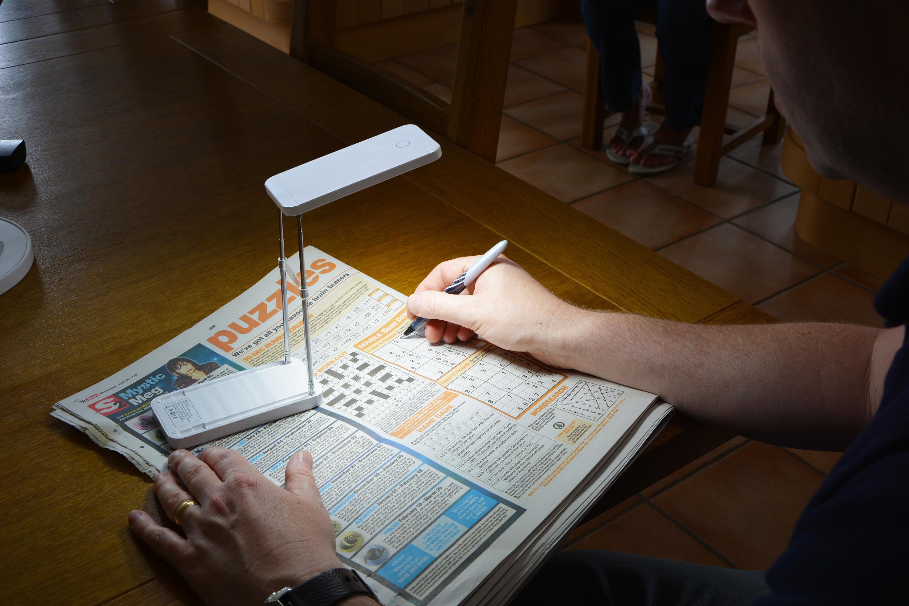 TravelBright 2 lighting up a newspaper crossword