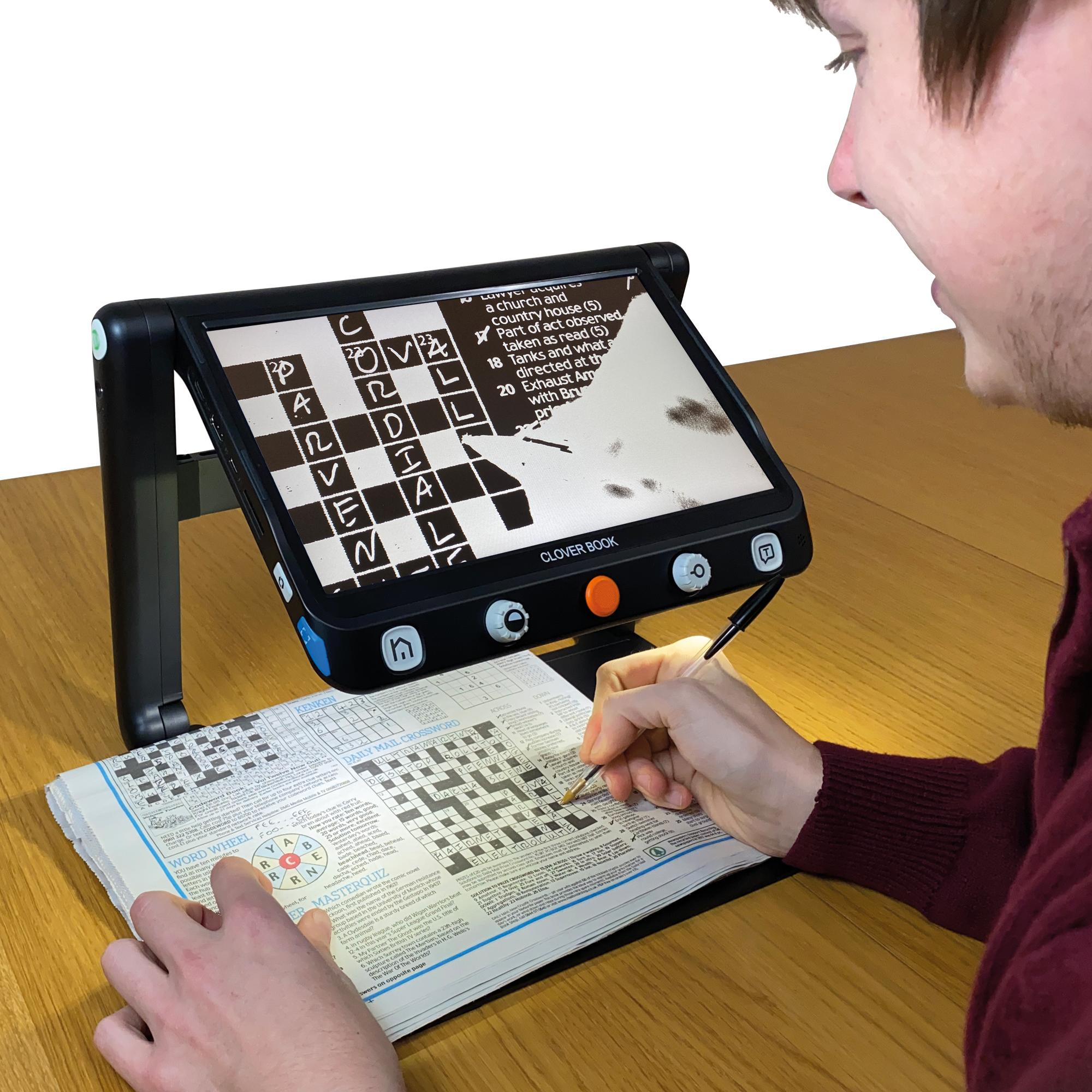 Clover Book magnifying a crossword with a man filling it in with a pen underneath the screen
