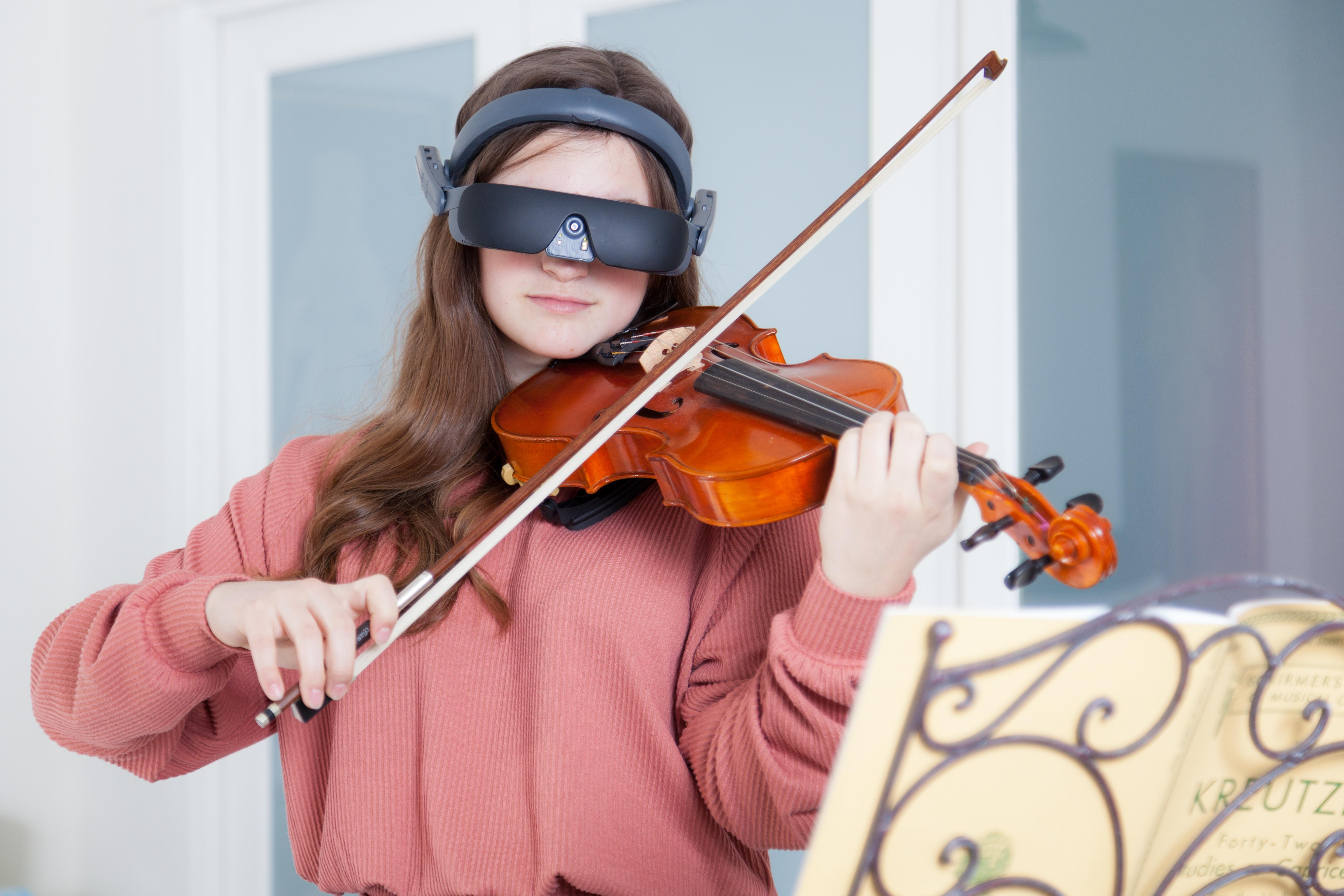 a young lady using the esigh 4 while playing her violin