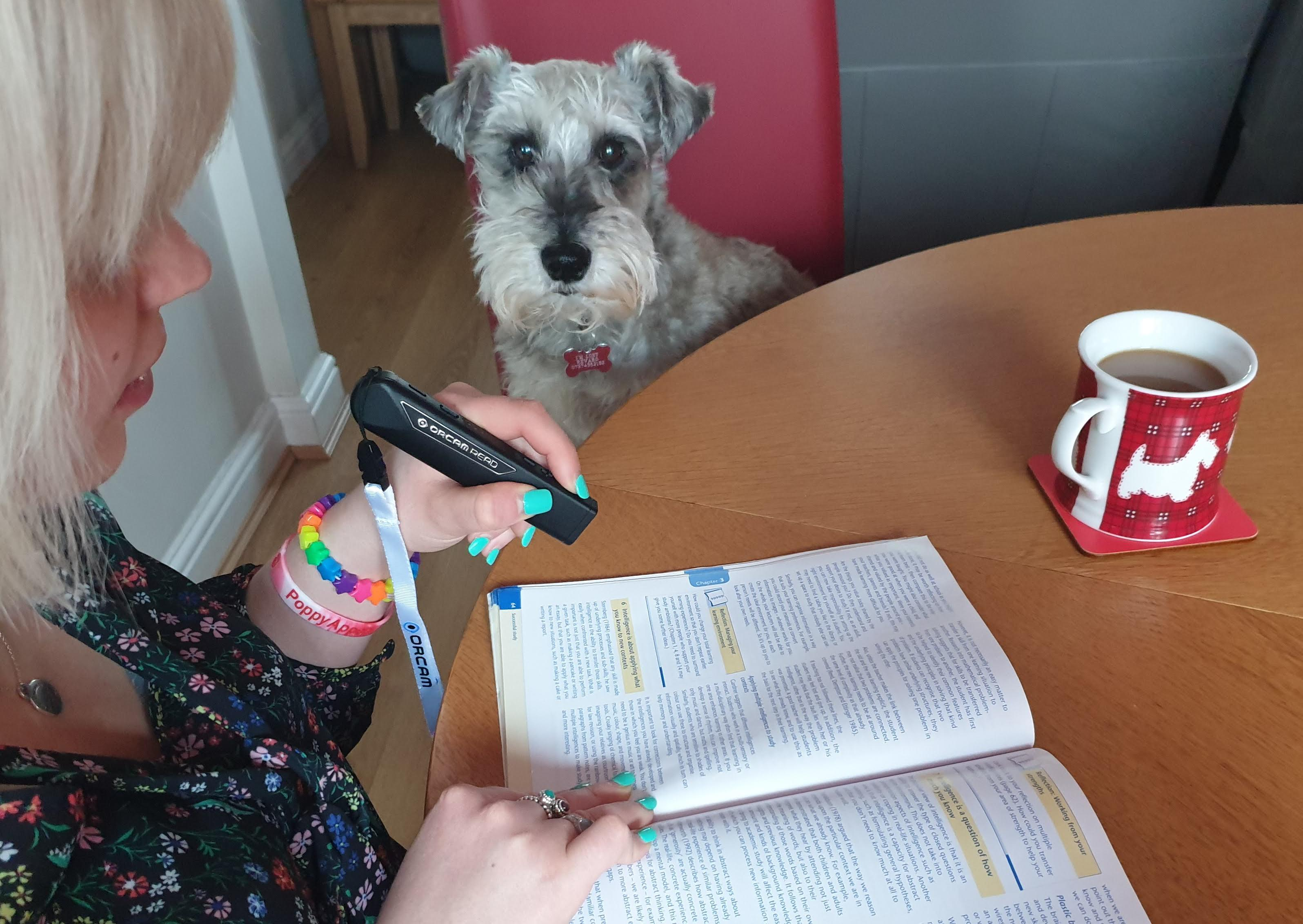 A Student using her VisionAid OrCam Read Smart - SpLD Edition (DSA) to read a workbook at home, there is a cup of coffee on the table and a schnauzer dog sat with her