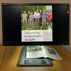 The Humanware Prodigi Duo displaying a magnified image of a magazine on it's 24 inch screen.
