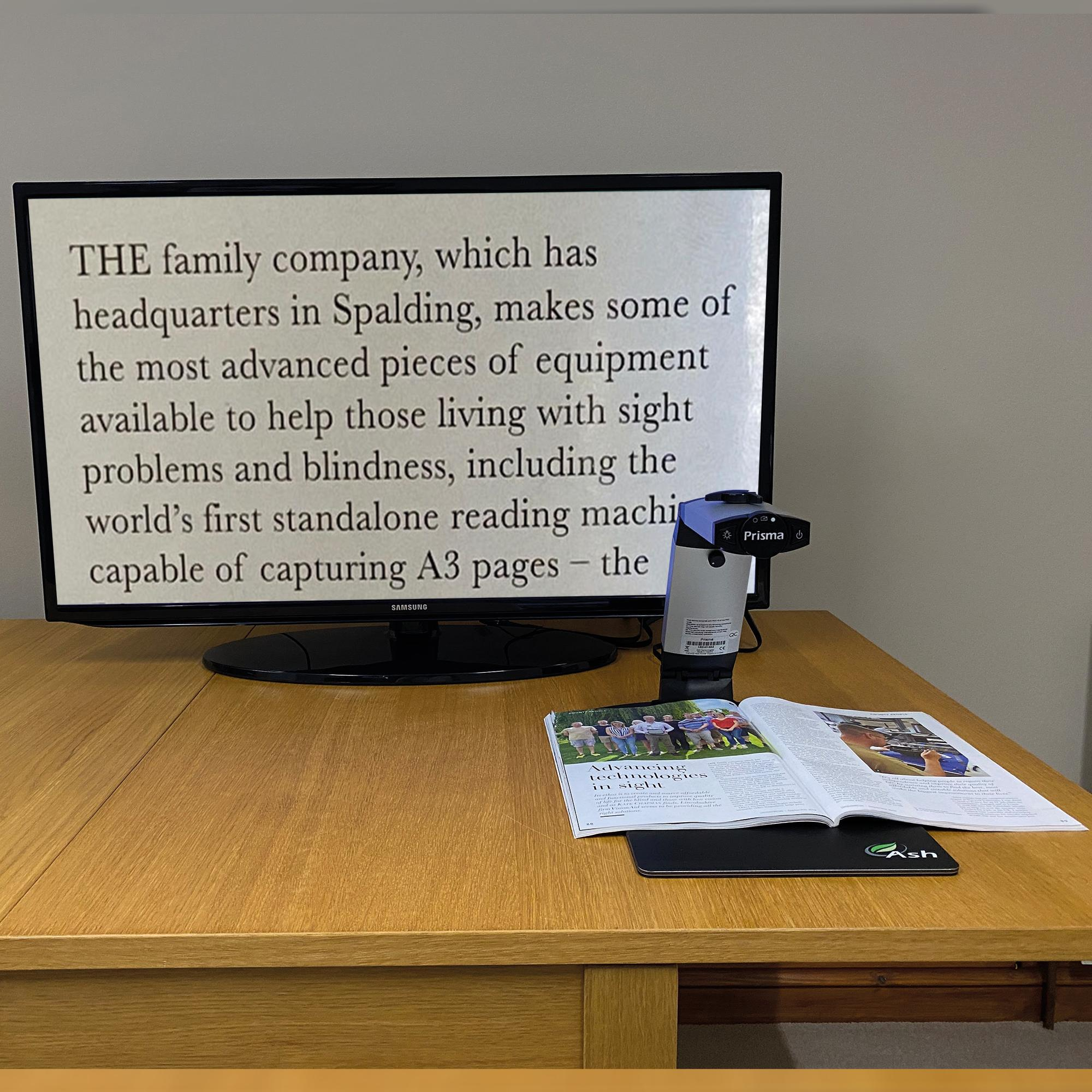 The Prisma displaying a magazine text on a large monitor. The Prisma can be plugged into computer monitors, or larger TVs for easier magnification.