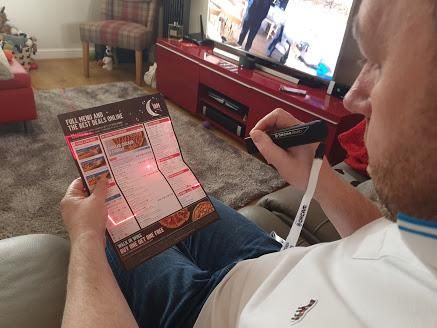a man using his orcam read smart to read a takeaway menu