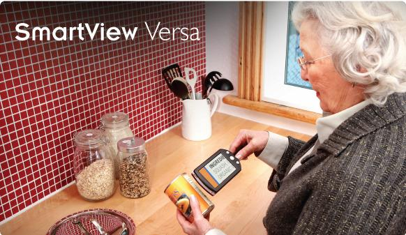 An elderly lady is using the SamrtView Versa to read a product in her kitchen