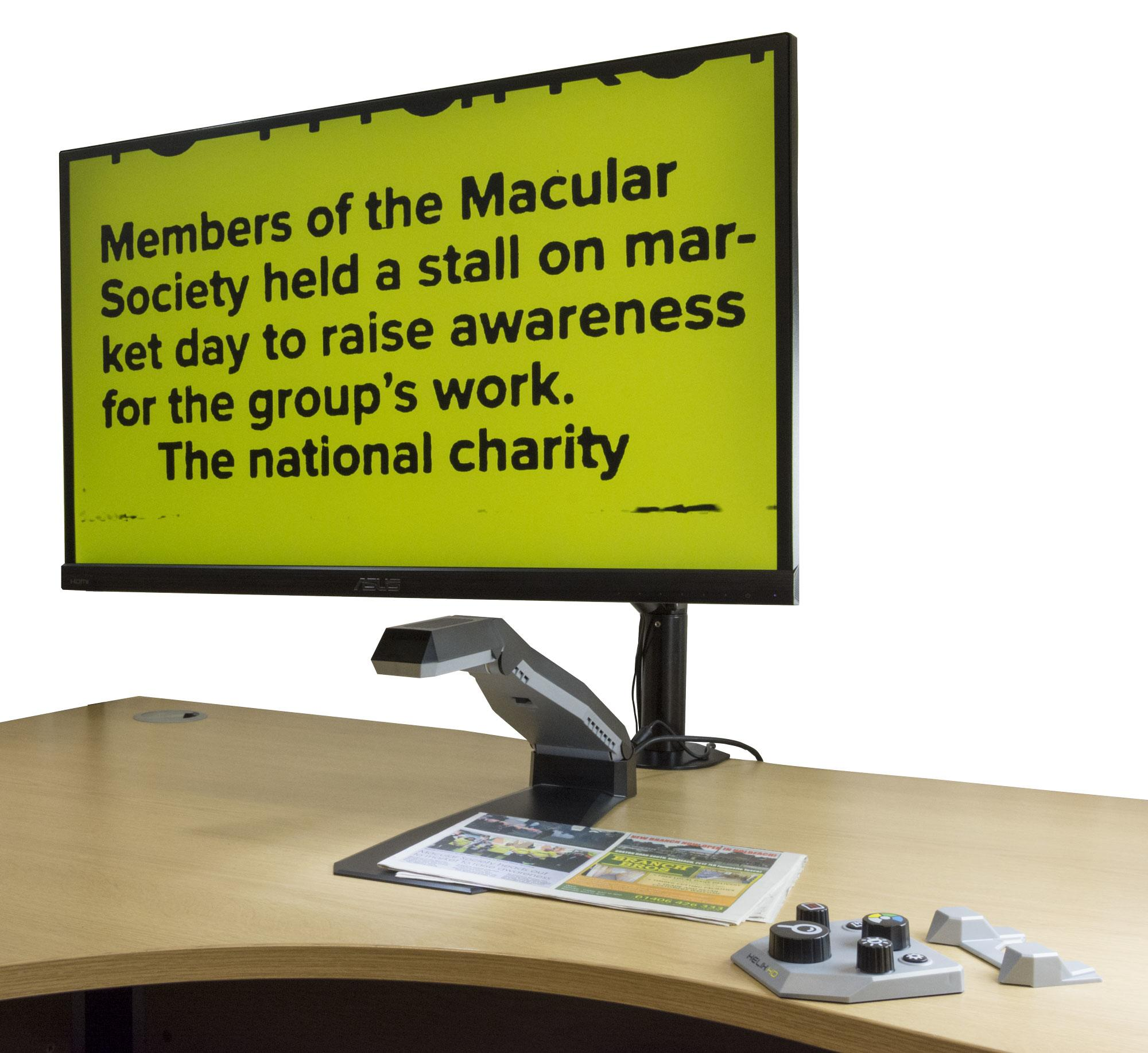 "Helix HD magnifying a newspaper article into black text on a yellow background onto a 27"" screen mounted to the VTArm 3 monitor arm."