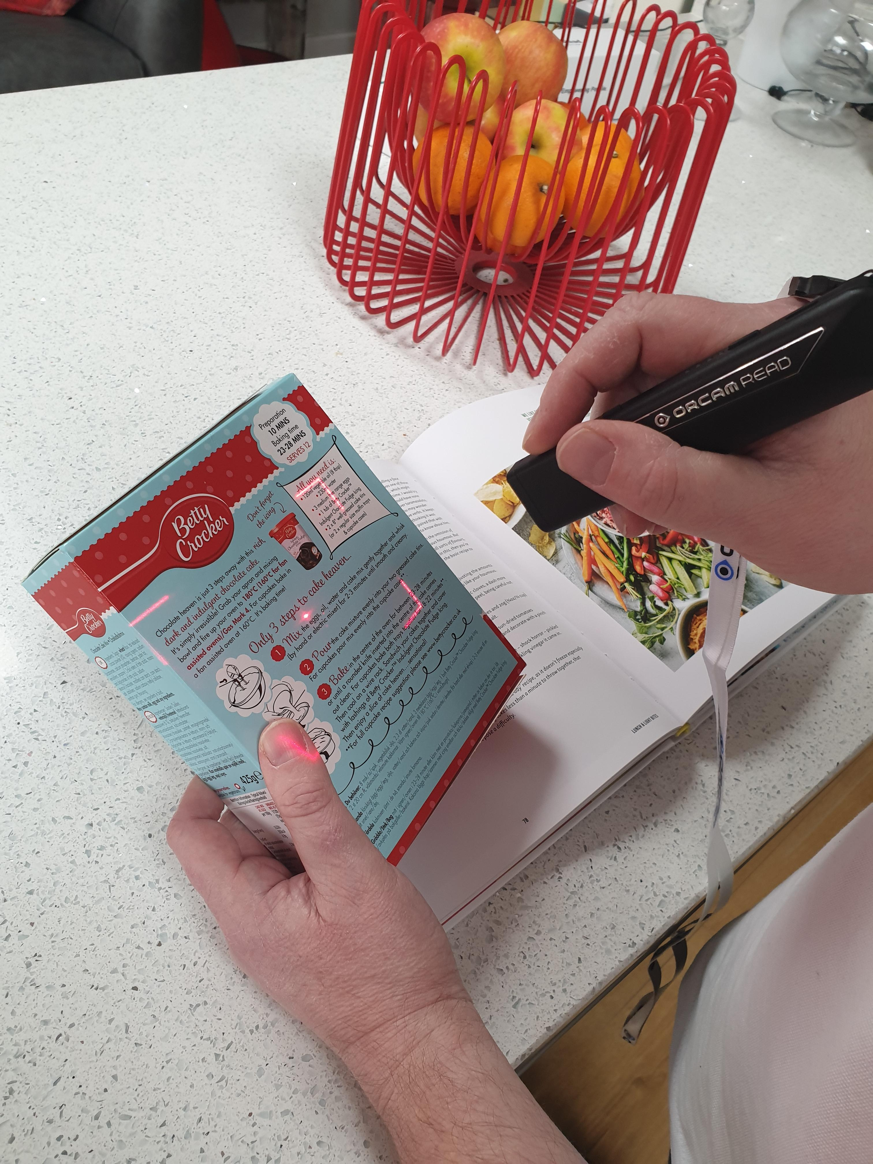 a man using his orcam read smart to read some packet instructions of a cake mixture