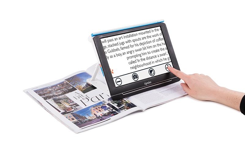 Compact 10 HD Speech magnifing some text in a magazine with its touch screen buttons visable on the screen