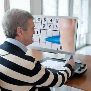 Reinecker VEO Vario Ultra HD being used to magnify a crossword