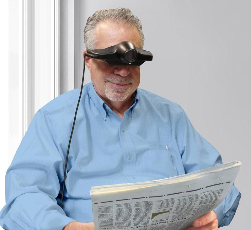 A man wearing a Jordy using it to read a newspaper