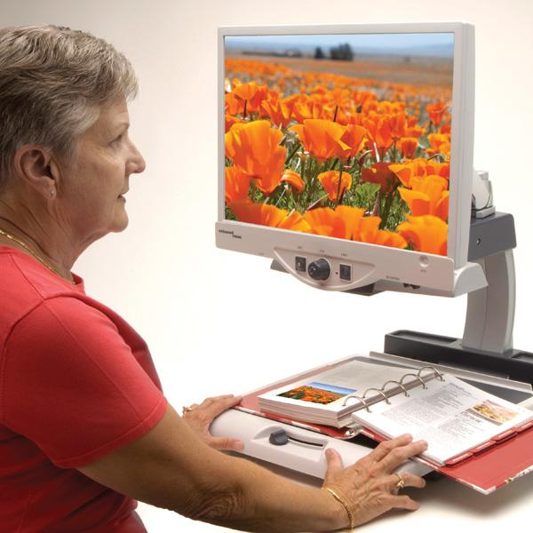Merlin Basic being used to magnify a picture from a book; a field of flowers