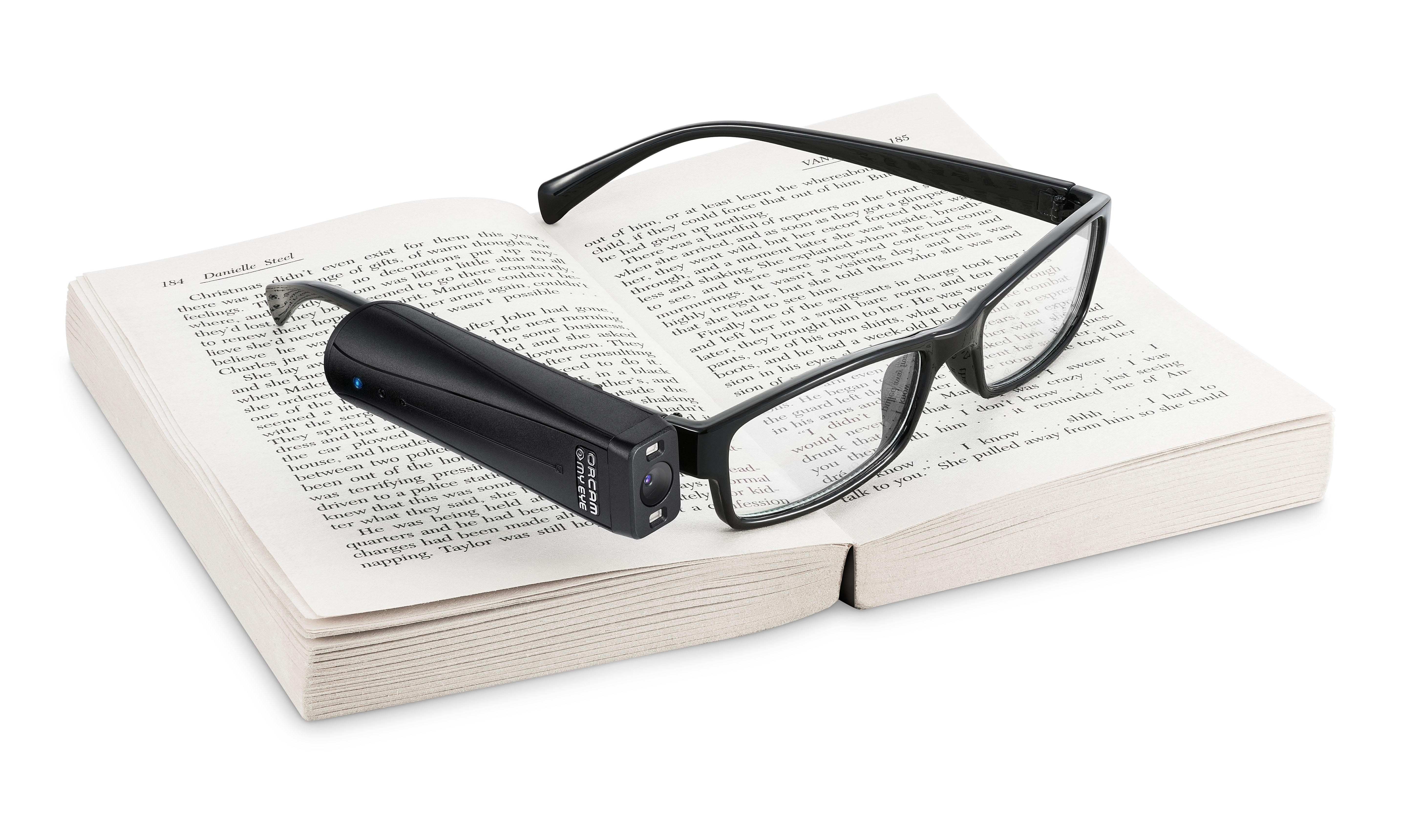 OrCam MyReader 2 on a pair of glasses resting on a book.