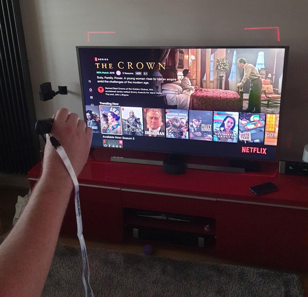 a man using his orcam read smart to read the tv listings on his tv screen