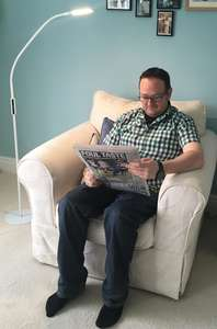 StandBright next to a man in an armchair lighting his newspaper
