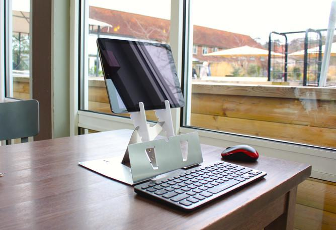 Arrow tablet stand shown on a desk with a wireless keyboard in front
