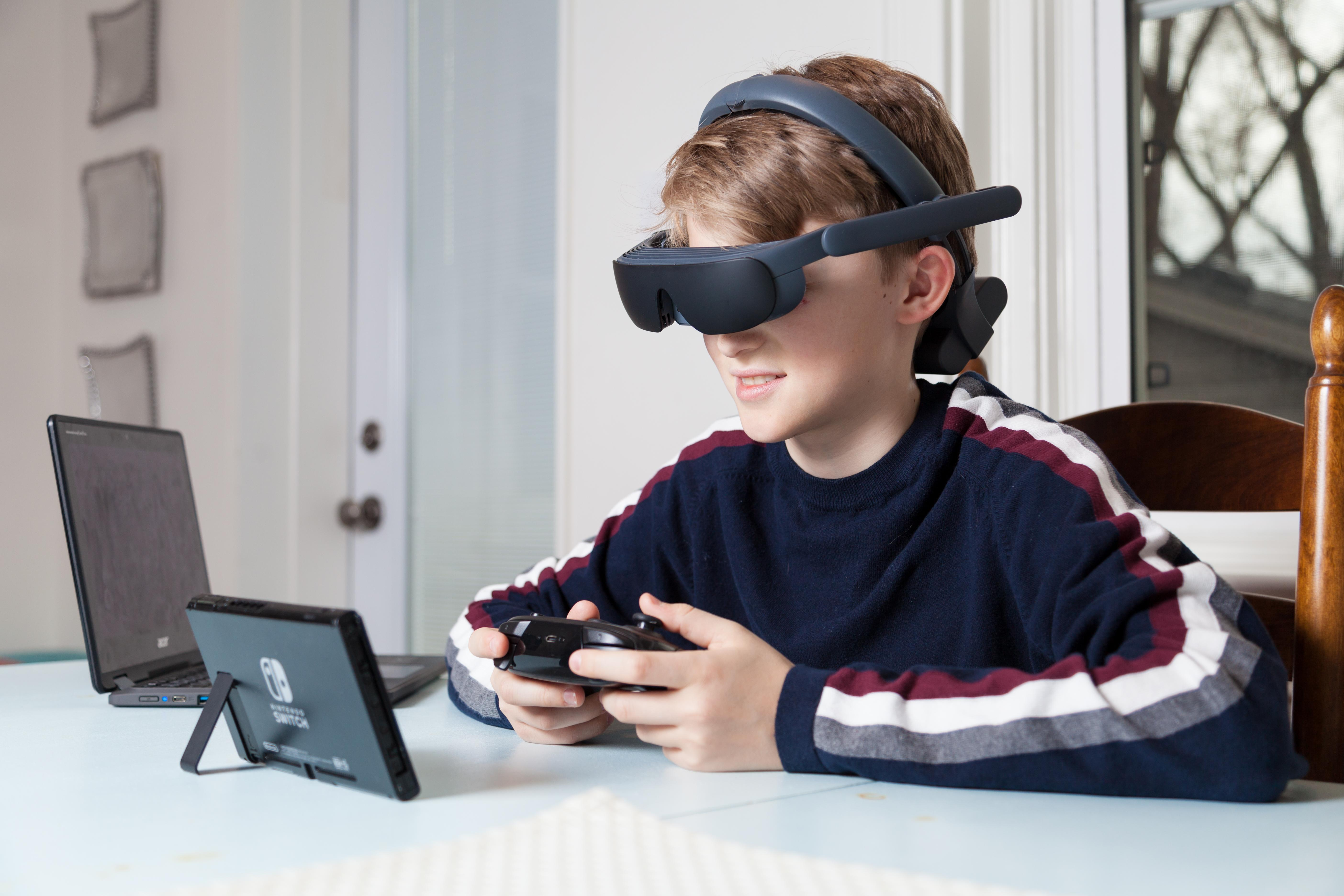 a young boy wearing the esight 4 to play the ninteno switch