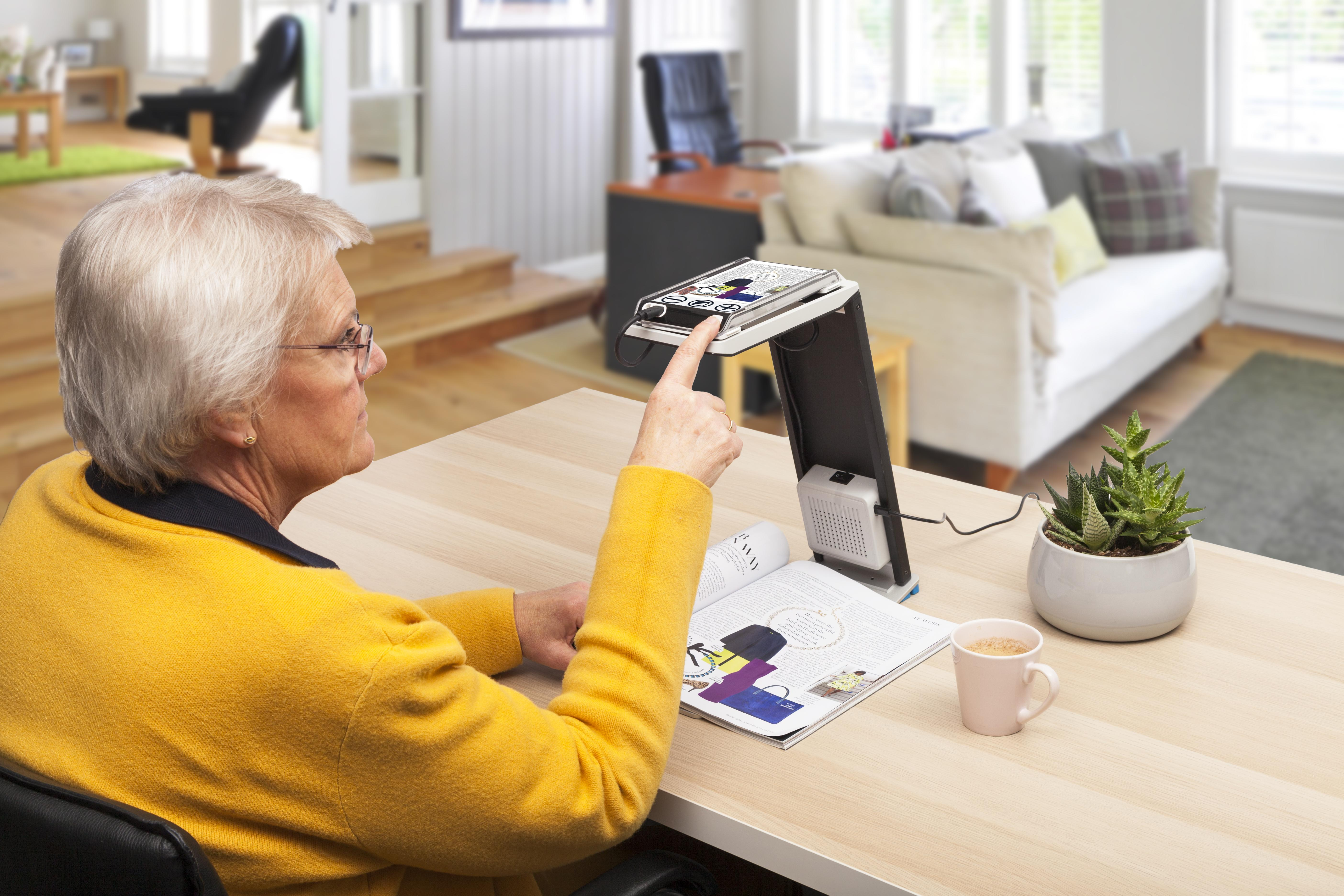 elderly lady using Compact 6 HD Speech Dock to read a magazine