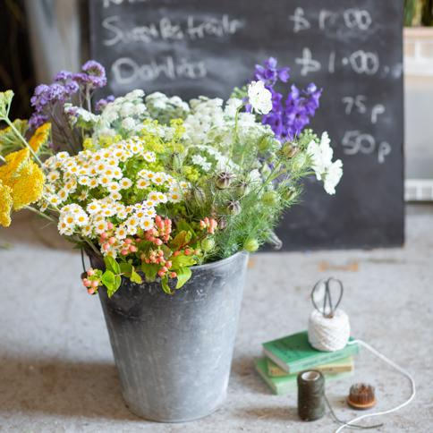 July flowers in yellow, white and purple bunches curated together as a flower arrangers bucket