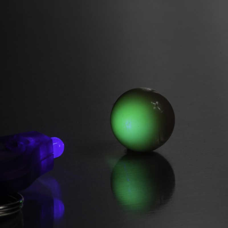 Uranium Glass Marble in darkness with a UV light shining on it which shows the fluorescence