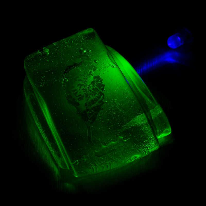A Uranium Glass ornament or paperweight in darkness with a UV light shining on it which shows the fluorescence