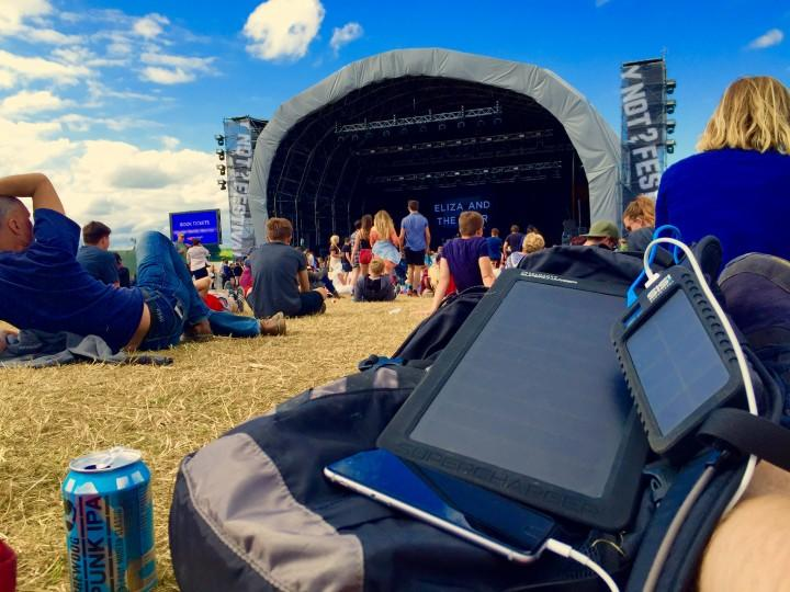 Freeloader Off Grid Adventurer charging a smart phone at a festival using the solar panel