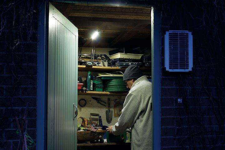 Man in garden shed working by light provided by the Hubi Work system