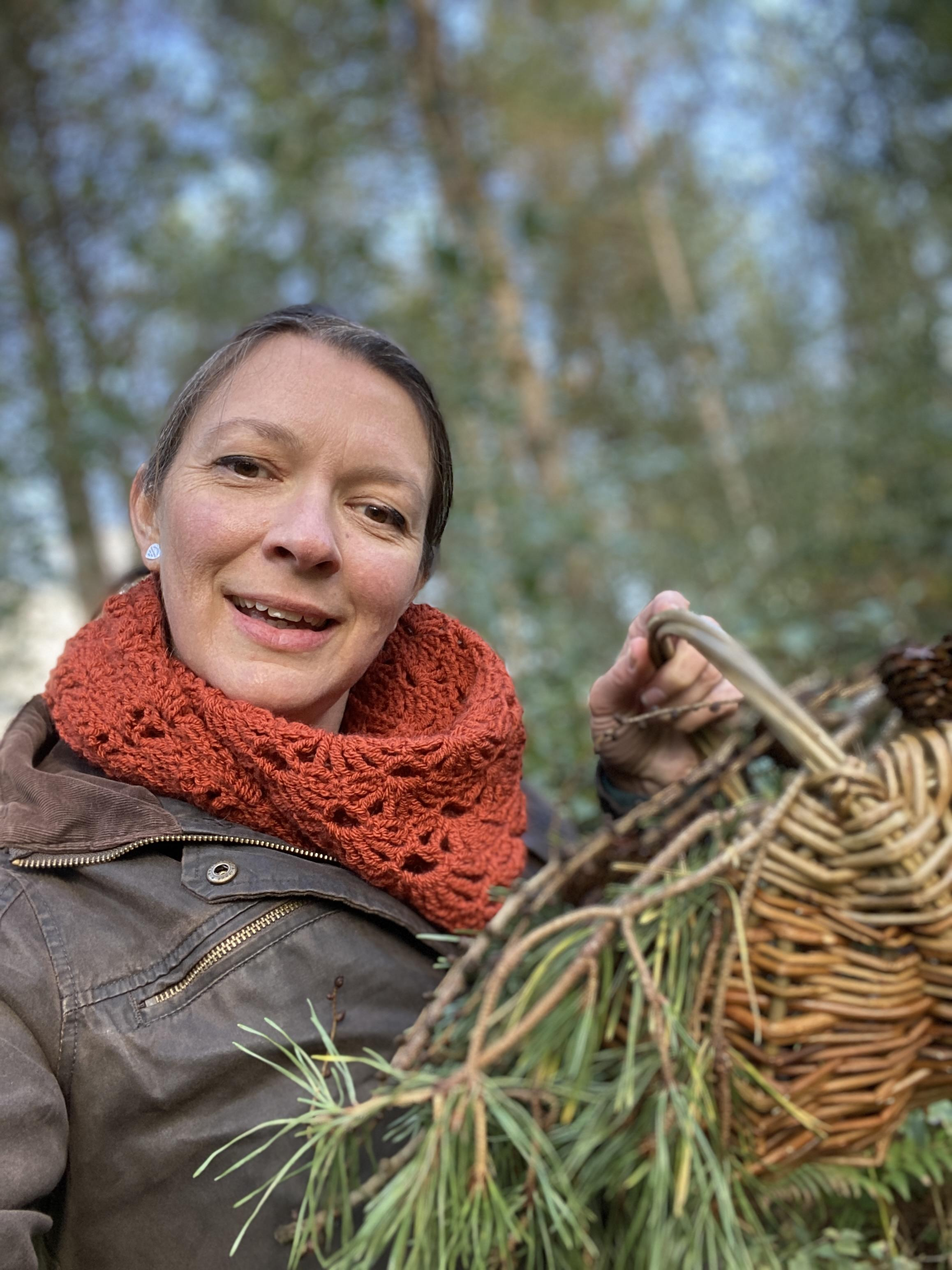Me showing my basket with autumnal leaves, wearing the Woodbury Castle shawl