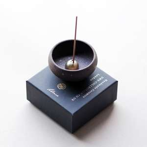 A small black clay bowl shown with brass dome incense holder inside with incense stick inserted on top of a black square gift box.