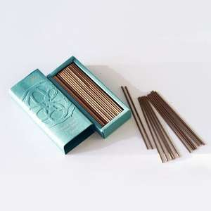 A pale green box open with the lid off showing brown incense sticks inside. Some incense sticks are scattered in a pile next to the box.