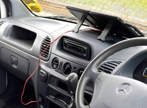 portable solar charger shown on car dash board