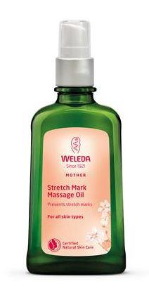 A green glass bottle with pink label and white atomiser. Label shows weleda stretch mark massage oil.