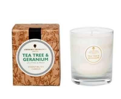 ivory candle in clear glass pot with natural brown box labelled amphora tea tree and geranium