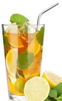 glass filled with orange clear liquid and fruit slices with mint leaves and ice, stainess steel straw stands in the drink