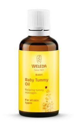 A small brown glass bottle with white cap, orange labelling shows weleda baby tummy oil.