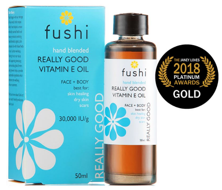 a brown glass bottle with black cap. stood next to light blue box packaging. Label shows fushi really good vitamin e oil.