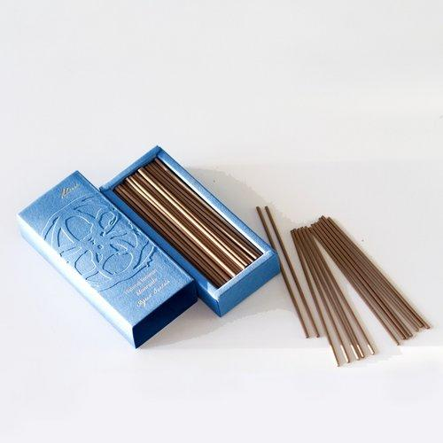 A pale blue rectangular box with lid off next to it. The open box is filled with long brown incense sticks. A few incense sticks are displayed in a pile next to the box.