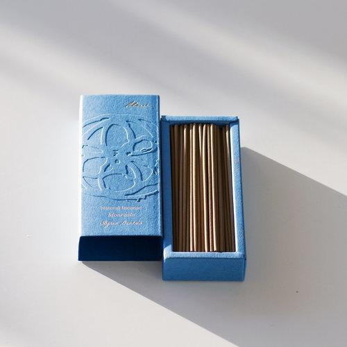 A pale blue rectangular box with lid off next to it. The open box is filled with long brown incense sticks.