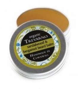 open aluminium jar showing yellow balm, black label showing trevarno organic sandalwood and bergamot beard balm