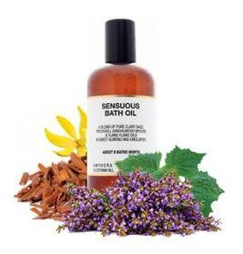 surrounded by herbs a brown plastic bottle with black cap and white label showing amphora sensuous bath oil