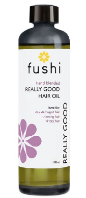 A brown glass bottle with black cap. Natural label has white flower image. Label shows Fushi really good hair oil.