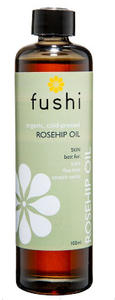 A brown glass bottle with black cap. Natural label has white flower image. Label shows Fushi organic rosehip seed oil.