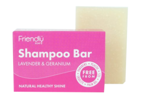 A bright pink box with white labelling next to a natural cream coloured rectangle bar of  soap. Labelling shows, Friendly Soap, Shampoo Bar.