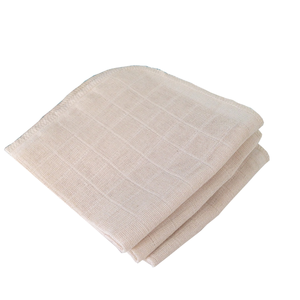 A pile of 3 folded natural cream coloured muslin cloths