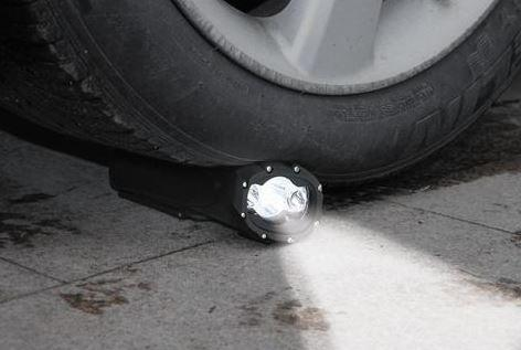 black heavy duty torch underneath a cars wheel