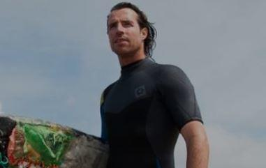 Dutch males surfer in black wetsuit holding surfboard made of recycled plastic waste