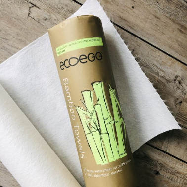 ecoegg bamboo towel roll shown in brown paper packaging on top of unrolled cream bamboo towel sheet.