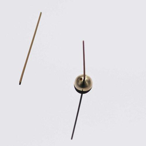 Small gold dome shaped incense holder, with incense stick inserted.