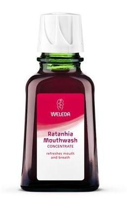 A green glass bottle with white cap. Red label shows weleda ratanhia mouthwash.