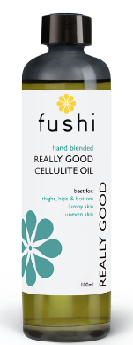 A brown glass bottle with black cap. Label shows fushi really good cellulite oil.